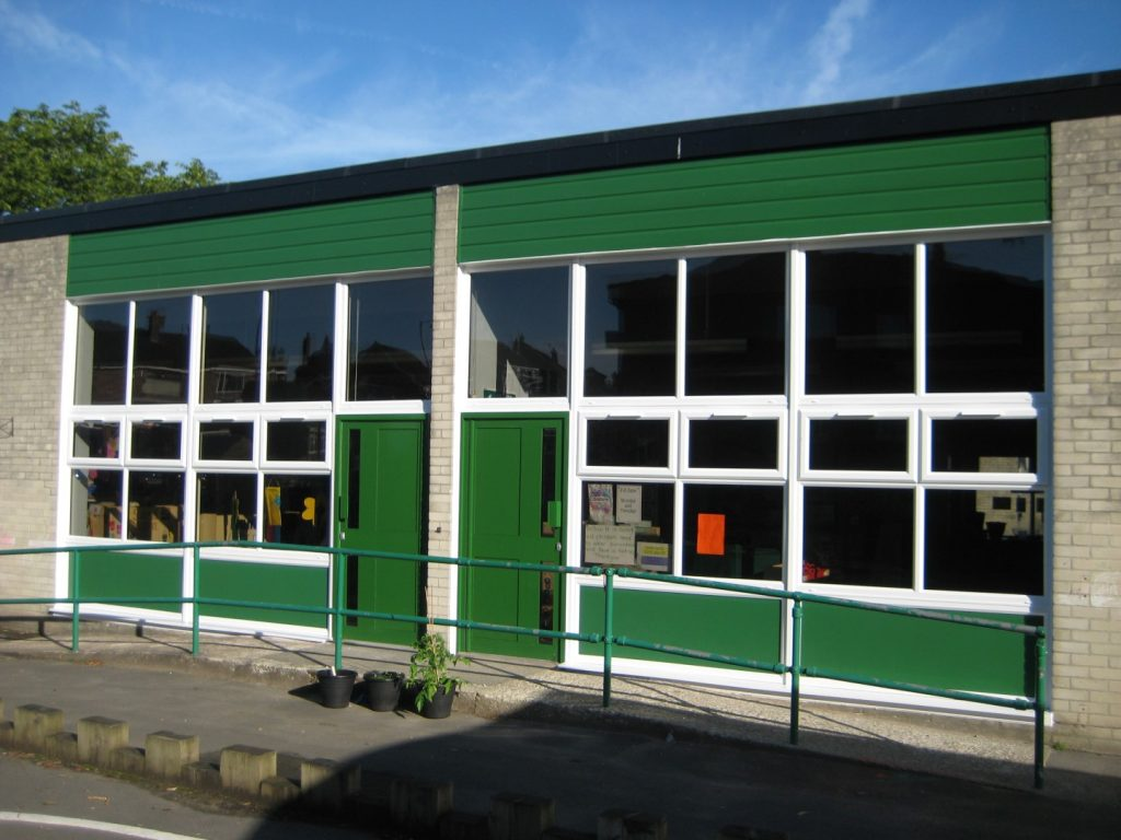White uPVC windows and bespoke green aluminium commercial doors