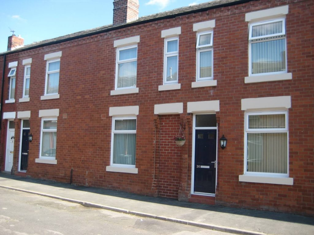 White casement windows on a red brick terraced property