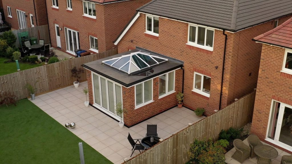 Modern orangery with white lantern roof and bifold doors